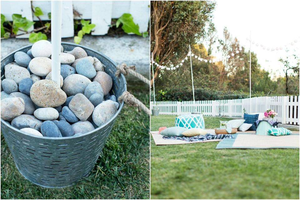 """<p>You don't need a covered patio to create some ambience. Fill buckets with stones to anchor a ring of <a href=""""https://www.goodhousekeeping.com/food-recipes/party-ideas/tips/a32365/emily-henderson-target-spring-entertaining/"""" rel=""""nofollow noopener"""" target=""""_blank"""" data-ylk=""""slk:festive party"""" class=""""link rapid-noclick-resp"""">festive party</a> lights. </p>"""