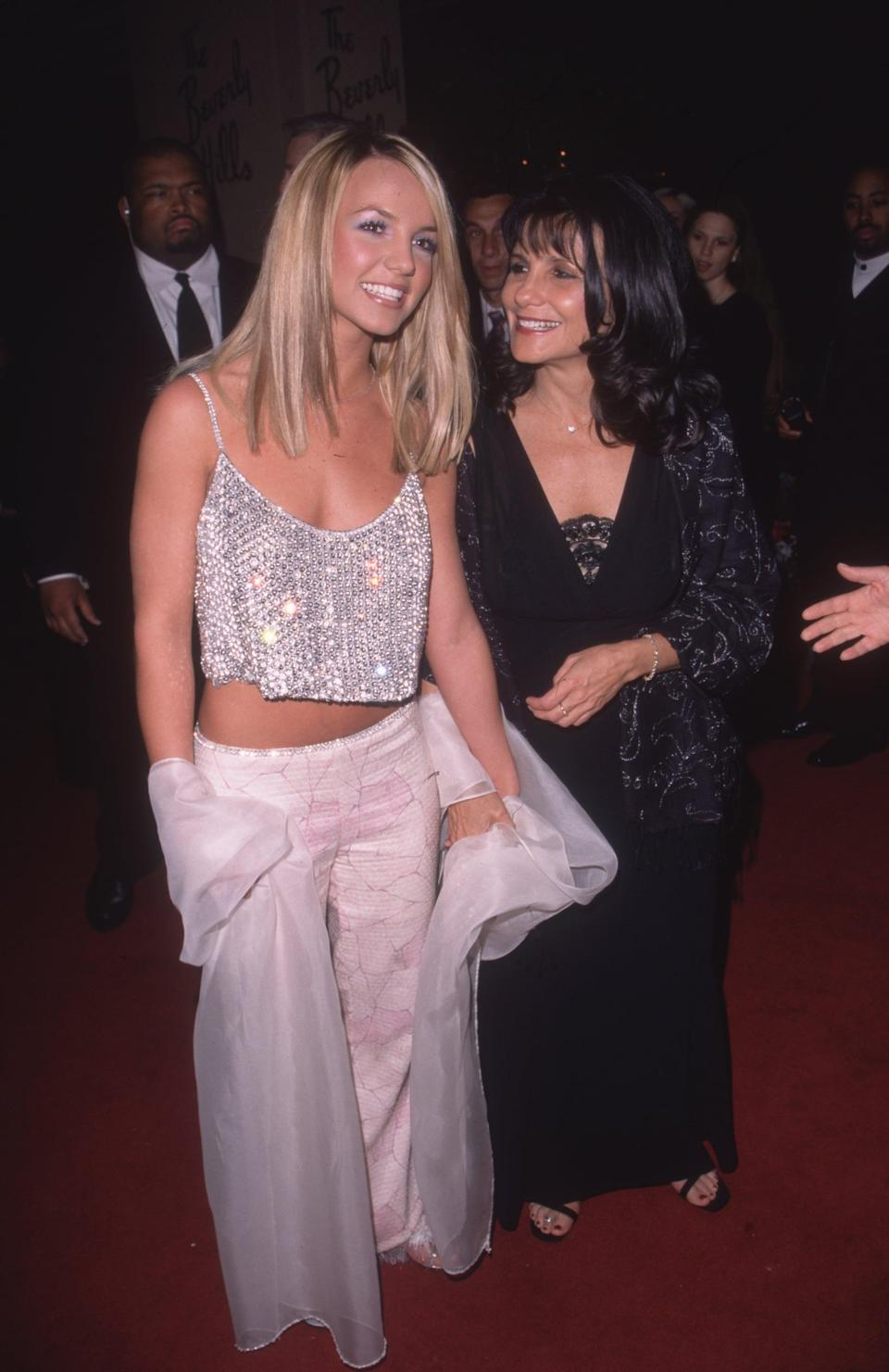 22nd February 2000:  Full-length image of American pop singer Britney Spears (L) with her mother Lynne Spears at the Arista Records pre-Grammy Awards party, Beverly Hills Hotel, Beverly Hills, California.  Britney was nominated for Best New Artist and Best Female Pop Vocal Performance. She is wearing a midriff-bearing silver rhinestone tank top, pink and white pants and a white shawl.  (Photo by Paul Skipper/Fotos International/Getty Images)
