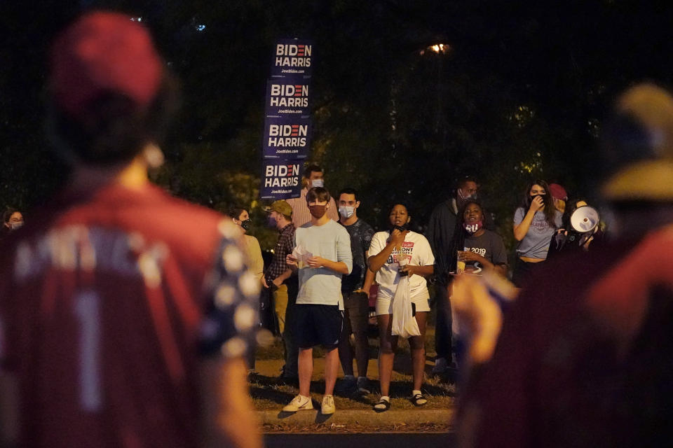 Supporters of former Vice President Joe Biden yell across the street at supporters of President Donald Trump in front of Belmont University during the second presidential debate Thursday, Oct. 22, 2020, in Nashville, Tenn. The debate was held in the Belmont basketball arena and event center. (AP Photo/Mark Humphrey)
