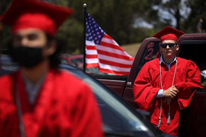 SAN RAFAEL, CALIFORNIA - JUNE 12: Redwood High School seniors look on during a drive-in graduation ceremony at the Marin County Fairgrounds on June 12, 2020 in San Francisco, California. Due to the coronavirus COVID-19 pandemic, Redwood High School graduating seniors had a drive-in ceremony where graduates had to practice social distancing and remain in or immediately around their vehicles with their families.  (Photo by Justin Sullivan/Getty Images)