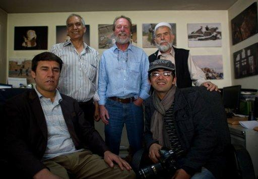 "Agence France-Presse (AFP) photographer Massoud Hossaini (R) poses with colleagues including Shah Marai (L) and Lawrence Bartlett (C) at the AFP office in Kabul. Hossaini won the Pulitzer award for breaking news photography ""for his heartbreaking image of a girl crying in fear after a suicide bomber's attack at a crowded shrine in Kabul,"" the committee announced"