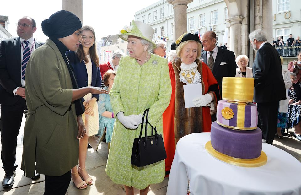 WINDSOR, ENGLAND - APRIL 21:  Queen Elizabeth II receives a birthday cake from Nadiya Hussain, winner of the Great British Bake Off, during her 90th Birthday Walkabout on April 21, 2016 in Windsor, England. Today is Queen Elizabeth II's 90th Birthday. The Queen and Duke of Edinburgh will be carrying out engagements in Windsor.  (Photo by John Stillwell - WPA Pool/Getty Images)