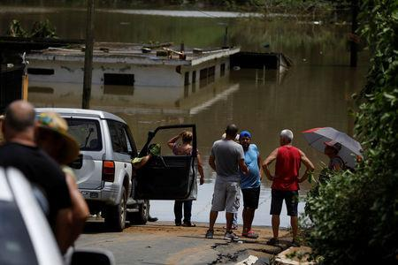 Local residents look at the flooded houses close to the dam of the Guajataca lake. REUTERS/Carlos Garcia Rawlins