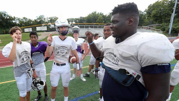 PHOTO: Bloomfield Hills' Dean Bolton, Santhosh Ramachandran and Tasnner Slazinski sign with Bloomfield Hills defensive lineman Devin Holmes, right, who is deaf, during practice on Wednesday, Sept. 4, 2019, at Bloomfield Hills High School. (Kirthmon F. Dozier/Detroit Free Press via Imagn Content Services, LLC)