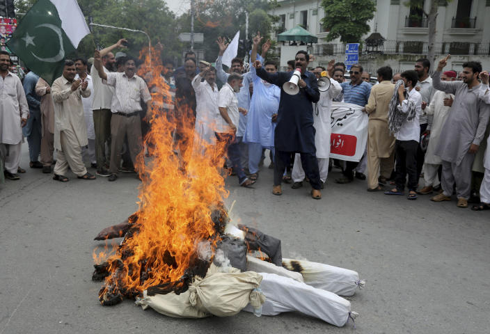 Pakistani clerks shout anti India slogans after burning effigies of Indian Prime Minster Narendra Modi during a protest to express support and solidarity with Indian Kashmiri people in their peaceful struggle for their right to self-determination, in Lahore, Pakistan, Tuesday, Aug. 6, 2019. India's government has revoked disputed Kashmir's special status by a presidential order as thousands of troops patrolled and internet and phone services were suspended in the region where most people oppose Indian rule. (AP Photo/K.M. Chaudary)