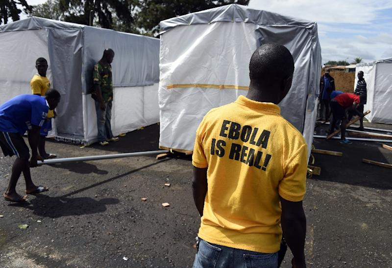 A man watches workers setting up a new treatment center as part of the fight against Ebola on September 28, 2014 in Monrovia (AFP Photo/Pascal Guyot)