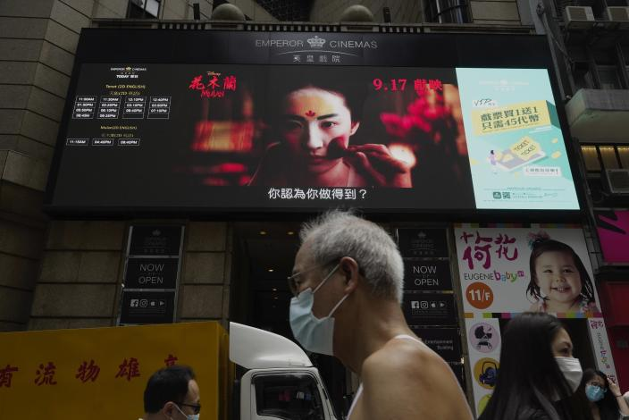 """FILE-In this Thursday, Sept. 17, 2020, file, People walk past a huge TV screen showing movie listings """"along a downtown street in Hong Kong. Hong Kong censors now have the power to ban films that endanger national security, prompting concerns that freedom of expression is being further curtailed in a city once known for its vibrant arts and film scene. (AP Photo/Vincent Yu, File)"""