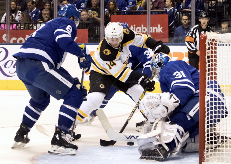 Toronto Maple Leafs goaltender Frederik Andersen (31) puts the stop on Boston Bruins right wing Chris Wagner (14) as Toronto Maple Leafs defenceman Jake Muzzin (8) looks on during first period NHL hockey action in Toronto, Saturday, Oct. 19, 2019. (Fred Thornhill/The Canadian Press via AP)