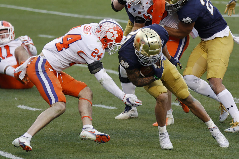 CHARLOTTE, NORTH CAROLINA - DECEMBER 19: Running back Kyren Williams #23 of the Notre Dame Fighting Irish is tackled by safety Nolan Turner #24 of the Clemson Tigers in the first half during the ACC Championship game at Bank of America Stadium on December 19, 2020 in Charlotte, North Carolina. (Photo by Jared C. Tilton/Getty Images)