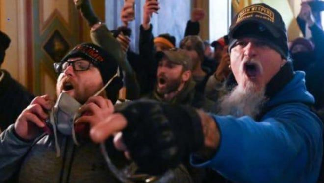 Jon Ryan Schaffer, right, one of the rioters who participated in the 6 January Capitol riot, screams and points after entering the federal building.  (FBI)