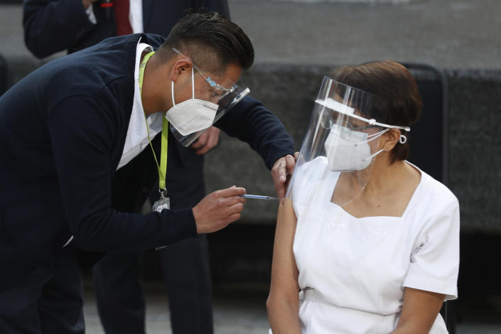 Health worker Maria Ramírez is the first to get vaccinated for COVID-19 at the General Hospital in Mexico City, early Thursday, Dec. 24, 2020. The first batches of vaccines produced by Pfizer and its German partner, BioNTech arrived the previous day. (AP Photo/Eduardo Verdugo)