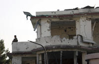 An Afghan national army soldier stands on the top of a damaged building following an attack in Kabul, Afghanistan, Wednesday, Aug. 4, 2021. A powerful explosion rocked an upscale neighborhood of Afghanistan's capital Tuesday in an attack that apparently targeted the country's acting defense minister. (AP Photo/Rahmat Gul)