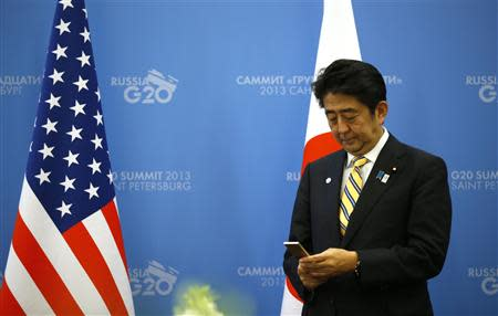 Japanese Prime Minister Shinzo Abe checks his phone while waiting for U.S. President Barack Obama (not seen) to arrive for their meeting at the G20 summit in St. Petersburg September 5, 2013. REUTERS/Kevin Lamarque