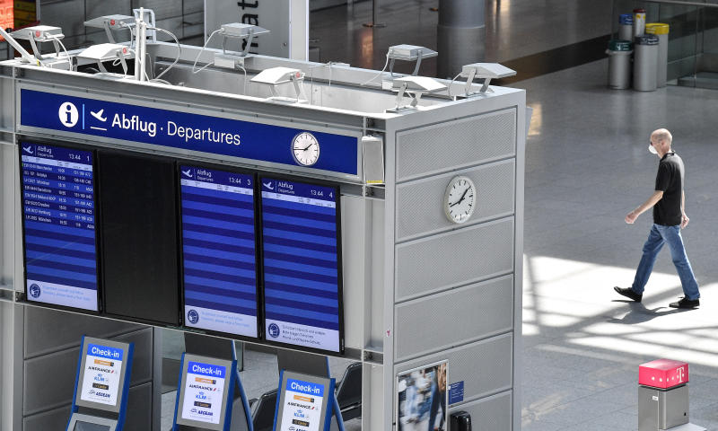 A man passes the empty departure information board at the airport in Duesseldorf, Germany, Wednesday, June 3, 2020. Germany is going to lift the travel ban in Europe on 15 June. (AP Photo/Martin Meissner)