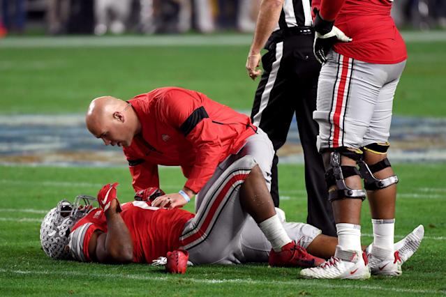 """Ohio State RB J.K. Dobbins is checked by the trainer against the <a class=""""link rapid-noclick-resp"""" href=""""/ncaaf/teams/clemson/"""" data-ylk=""""slk:Clemson Tigers"""">Clemson Tigers</a> in the first half during the College Football Playoff Semifinal. (Photo by Norm Hall/Getty Images)"""