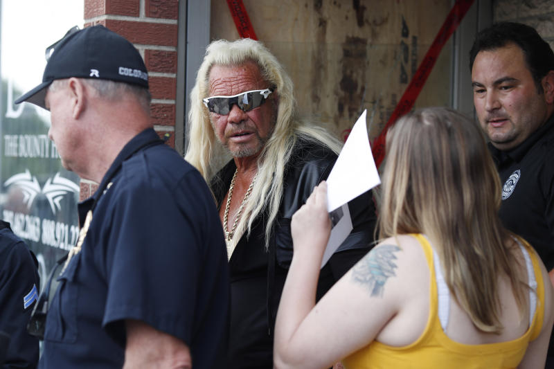 """Duane """"Dog the Bounty Hunter"""" Chapman, back, charts with his daughter, Bonnie Jo, outside his storefront that was burglarized before a news conference Friday, Aug. 2, 2019, in Edgewater, Colo. Police in Colorado said Friday they are investigating a reported burglary of a business owned by """"Dog the Bounty Hunter"""" reality TV star Duane """"Dog"""" Chapman. (AP Photo/David Zalubowski)"""