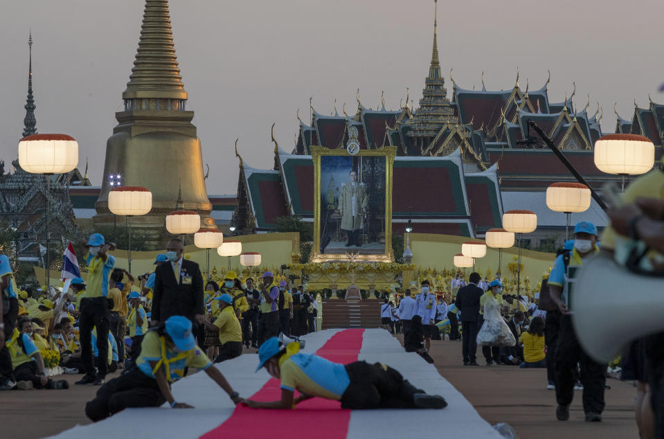 Officials adjust a carpet as late King Bhumibol Adulyadej's images is displayed in the background ahead of the arrival of King Maha Vajiralongkorn and Queen Suthida to participate in a candle lighting ceremony to mark birth anniversary of late King Bhumibol Adulyadej at Sanam Luang ceremonial ground in Bangkok, Thailand, Saturday, Dec. 5, 2020. (AP Photo/Gemunu Amarasinghe)