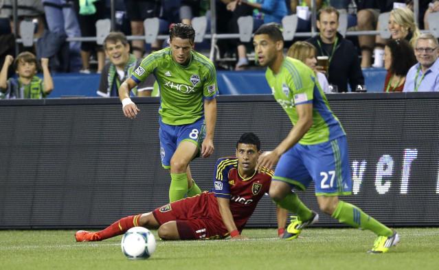Real Salt Lake's Javier Morales, center, watches after going down in a battle for the ball with Seattle Sounders' Marc Burch, left, and Lamar Neagle, right, in the first half of an MLS soccer match, Friday, Sept. 13, 2013, in Seattle. (AP Photo/Ted S. Warren)