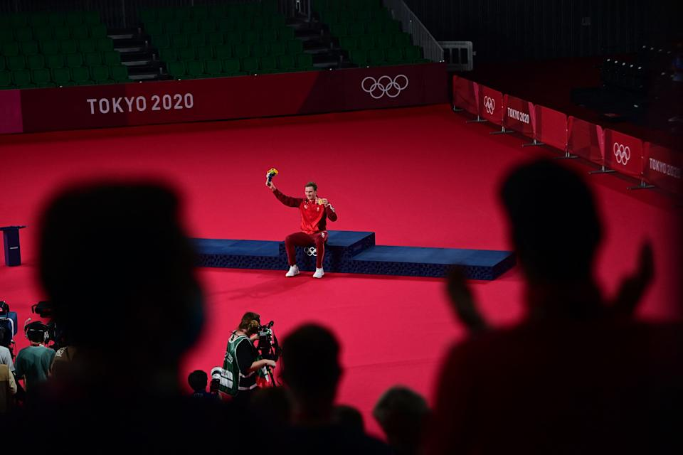 <p>TOPSHOT - Denmark's Viktor Axelsen is applauded with his men's singles badminton gold medal at a ceremony during the Tokyo 2020 Olympic Games at the Musashino Forest Sports Plaza in Tokyo on August 2, 2021. (Photo by Pedro PARDO / AFP) (Photo by PEDRO PARDO/AFP via Getty Images)</p>