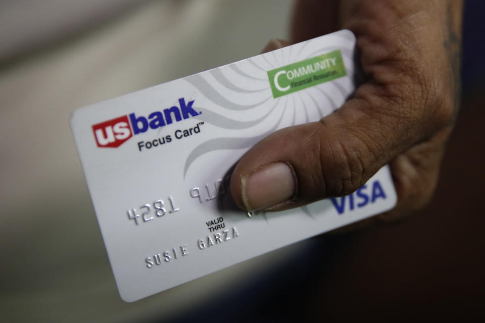 FILE - In this Aug. 14, 2019, file photo, Susie Garza displays the city provided debit card she receives monthly through a trial program in Stockton, Calif. A study of people in California who received $500 a month for free says they used it to pay off debt and get full-time jobs. A pair of independent researchers reviewed data from the first year of the study and released their finding on Wednesday, March 3, 2021. (AP Photo/Rich Pedroncelli, File)