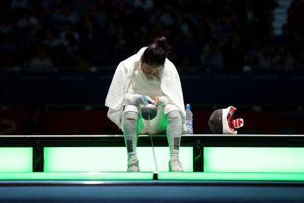 LONDON, ENGLAND - JULY 30:  A Lam Shin of Korea sits and waits to hear the outcome of an appeal to overturn the judges ruling on an issue of a delayed clock that caused her to loss her bout against Britta Heidemann of Germany during the Women's Epee Individual Fencing Semifinals on Day 3 of the London 2012 Olympic Games at ExCeL on July 30, 2012 in London, England. Heidemann scored the final point with one second left on the clock to win against Shin.  (Photo by Hannah Johnston/Getty Images)
