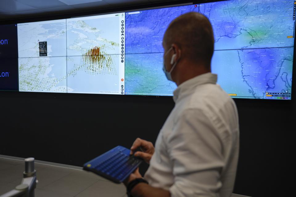 A police officer monitors screens showing the flow of people and web cameras at a police station, in Venice, Italy, Thursday, June 17, 2021. After a 15-month pause in mass international travel, Venetians are contemplating how to welcome visitors back to the picture-postcard canals and Byzantine backdrops without suffering the indignities of crowds clogging its narrow alleyways, day-trippers perched on stoops to imbibe a panino and hordes of selfie-takers straining for a spot on the Rialto Bridge or in front of St. Mark's Basilica. (AP Photo/Luca Bruno)