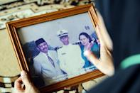 A family member holds a photograph of Marine Colonel Harry Setiawan, commander of the Indonesian navy's KRI Nanggala submarine