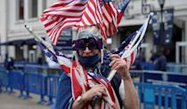 A fan holds US flags in front of Yankee Stadium in New York on April 1, 2021