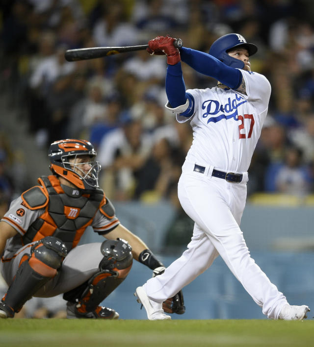 Los Angeles Dodgers' Alex Verdugo, right, follows through on a swing for a solo home run while San Francisco Giants center Buster Posey looks on during the fifth inning of a baseball game in Los Angeles, Monday, April 1, 2019. (AP Photo/Kelvin Kuo)