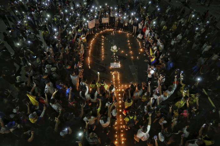 People light candles during a vigil in honor of Nicolas Guerrero who died after being shot during a national strike against tax reform in Cali, Colombia, Monday, May 3, 2021. Guerrero was shot during clashes with police on Sunday and died this morning. Colombia's President Ivan Duque withdrew the government-proposed tax reform on Sunday. (AP Photo/Andres Gonzalez)