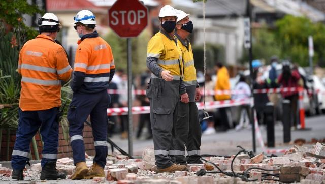 Emergency workers were seen surveying the damage in Melbourne after part of a wall fell from a building during the earthquake. AP