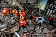 National Disaster Response Force (NDRF) officials and firemen remove debris as they look for survivors after a three-storey residential building collapsed in Bhiwandi on the outskirts of Mumbai, India