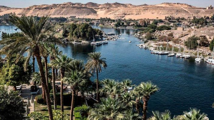 """This picture taken on January 3, 2021 shows a view of Aswan from the Old Cataract Hotel overlooking the Nile river in Egypt's southern city of Aswan, some 920 kilometres south of the capital, where British crime fiction writer Dame Agatha Christie is believed to have stayed while writing her 1937 novel """"Death on the Nile"""", with the Mausoleum of Aga Khan III seen in the background (top R)."""