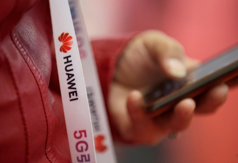 An attendee wears a badge strip with the logo of Huawei and a sign for 5G at the World 5G Exhibition in Beijing