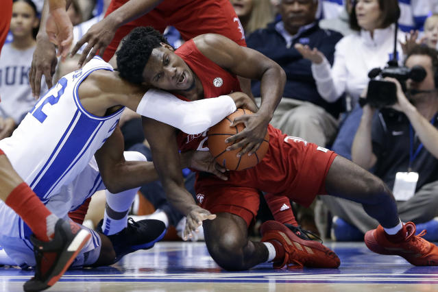 Duke forward Javin DeLaurier, left, and Louisville guard Darius Perry struggle for the ball during the first half of an NCAA college basketball game in Durham, N.C., Saturday, Jan. 18, 2020. (AP Photo/Gerry Broome)