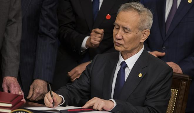 Chinese Vice-Premier Liu He, signing the trade agreement, was much in demand on Wednesday, with Chinese protesters chanting his name outside the White House a few yards away. Photo: Bloomberg