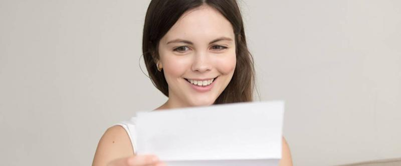 Surprised woman reading letter with unexpected good news, feeling excited about unbelievable offer in written notification, happy teenager