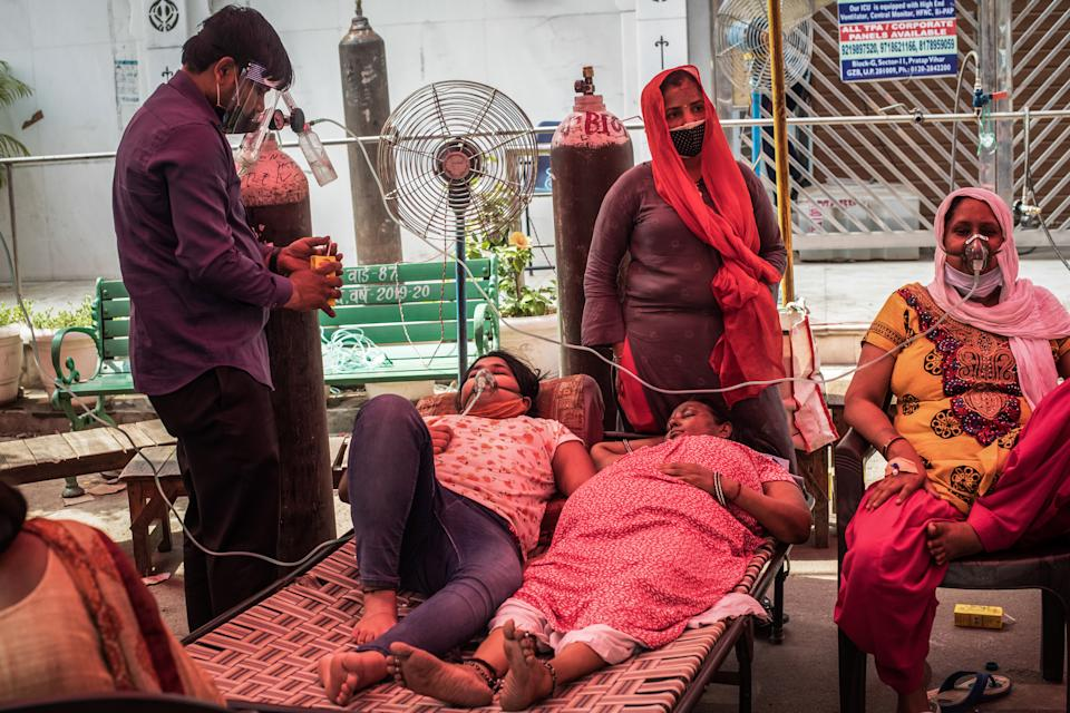 INDIRAPURAM, INDIA - MAY 02: Patients suffering from Covid-19 are treated with free oxygen at a makeshift clinic outside the Shri Guru Singh Sabha Gurdwara on May 02, 2021 in Indirapuram, Uttar Pradesh, India. With cases crossing 400,000 a day and with more than 3500 deaths recorded in the last 24 hours, India's Covid-19 crisis is intensifying and shows no signs of easing pressure on the country. A new wave of the pandemic has totally overwhelmed the country's healthcare services and has caused crematoriums to operate day and night as the number of victims continues to spiral out of control. (Photo by Rebecca Conway/Getty Images)