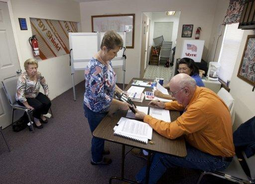 Poll workers check the identification of a voter in the tiny precinct of Smith Creek