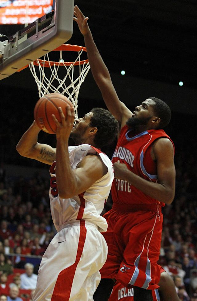 Dayton's Devin Oliver (5) tries to shoot while defended by Delaware State's Casey Walker in the first half of an NCAA college basketball game on Wednesday, Dec. 4, 2013, in Dayton, Ohio. (AP Photo/Skip Peterson)