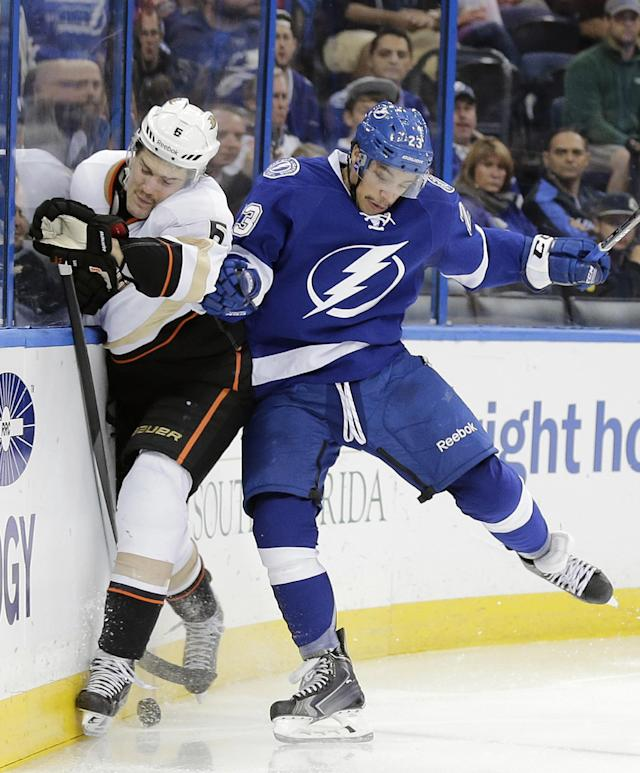 Tampa Bay Lightning right wing J.T. Brown (23) checks Anaheim Ducks defenseman Ben Lovejoy (6) into the boards during the second period of an NHL hockey game on Thursday, Nov. 14, 2013, in Tampa, Fla. (AP Photo/Chris O'Meara)