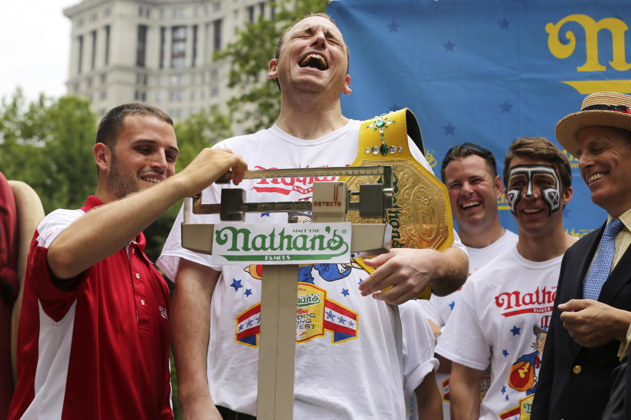 Joey Chestnut laughs as he stands on the scale during the official weigh-in for the Nathan's Fourth of July hot dog eating contest, Wednesday, July 3, 2013 at City Hall park in New York. (AP Photo/Mary Altaffer)