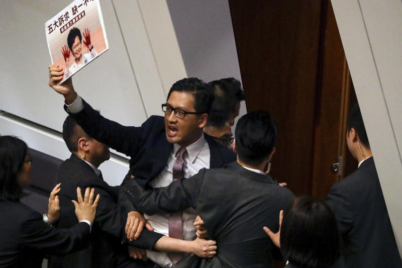A pro-democracy lawmaker is forcibly removed from the chamber of the Legislative Council for interrupting Hong Kong Chief Executive Carrie Lam attending a question and answer session in Hong Kong, Thursday, Oct. 17, 2019. (AP Photo/Mark Schiefelbein)