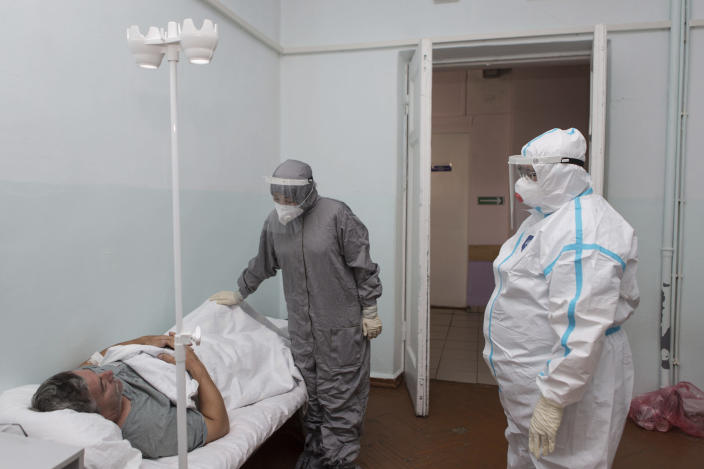 """Dr. Tatyana Symbelova, right, and another medical worker talk to a patient during a daily examination of patients suspected of having coronavirus in the red zone of the hospital in Ulan-Ude, the regional capital of Buryatia, a region near the Russia-Mongolia border, Russia, Friday, Nov. 20, 2020. Symbelova told the AP that as the number of patients rose, her hospital kept adding beds — """"in the corridor, in the outpatient ward next door"""" — but """"the situation, still, grew worse and worse."""" (AP Photo/Anna Ogorodnik)"""
