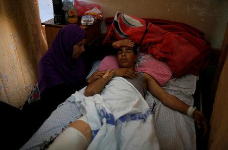 The mother of an injured Palestinian sits next to him as he lies on a bed at a hospital in Gaza City May 15, 2018. REUTERS/Mohammed Salem