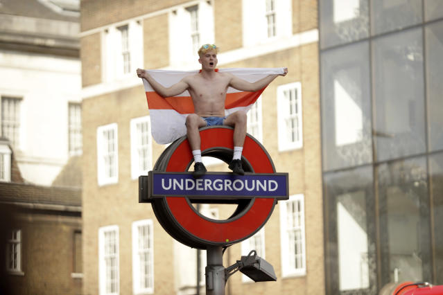 An England soccer fan sits with a St George's Cross England flag atop of a London Underground subway sign in the London Bridge area of London after England won their quarterfinal match against Sweden, at the 2018 soccer World Cup, Saturday, July 7, 2018. (AP Photo/Matt Dunham)