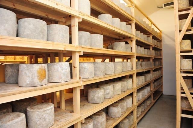 Cheeses mature in a store room (Ben Birchall/PA)
