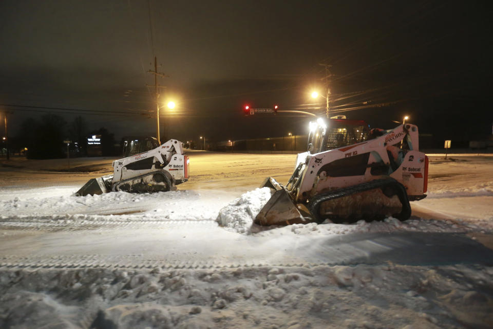 Crews with Tupelo Public Works begin to clear the intersection of South Green and Eason Blvd., Monday night, Feb. 15, 2021, as they work through the night to make the roads safe for travel in Tupelo, Miss. (Thomas Wells/The Northeast Mississippi Daily Journal via AP)