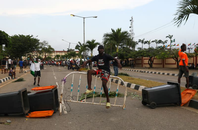 A demonstrator sits on a barricade blocking a road near the Lagos State House,