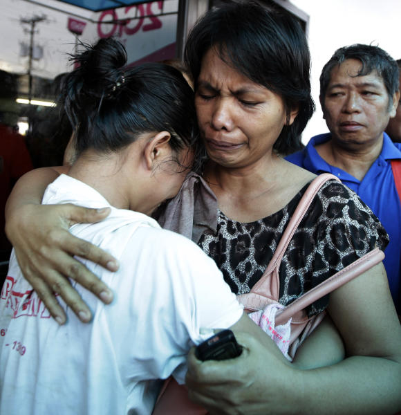 A survivor, left, of the ill-fated passenger ferry MV Thomas Aquinas, is comforted by a relative outside the ticketing office of a shipping company, Saturday Aug. 17, 2013, a day after the ferry collided with a cargo ship, the MV Sulpicio Express Siete, off the waters of Talisay city, Cebu province in central Philippines. Divers combed through the sunken ferry Saturday in search of dozens of people missing after the collision that sent passengers jumping into the ocean and leaving many others trapped. At least 31 were confirmed dead and hundreds rescued. (AP Photo/Bullit Marquez)